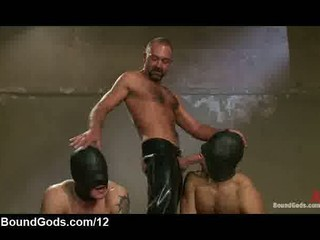 two gays with leather hoods electrified by masters